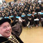 Sr. Arvid Johnson smiling with graduates