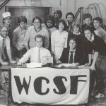 smiling students behind table with wcsf banner