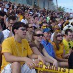 group of smiling students at homecoming football game
